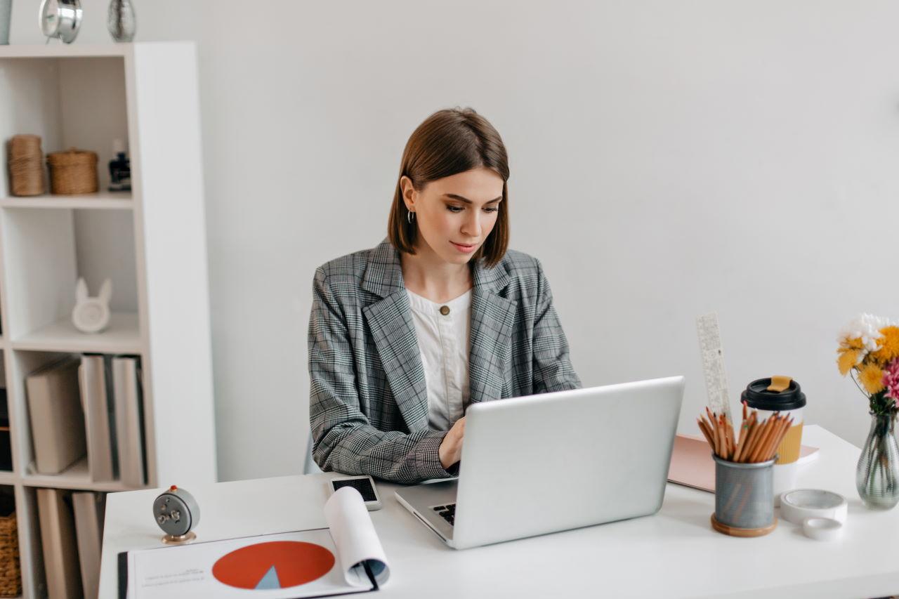 Business lady in gray jacket working in laptop. Portrait of woman in office