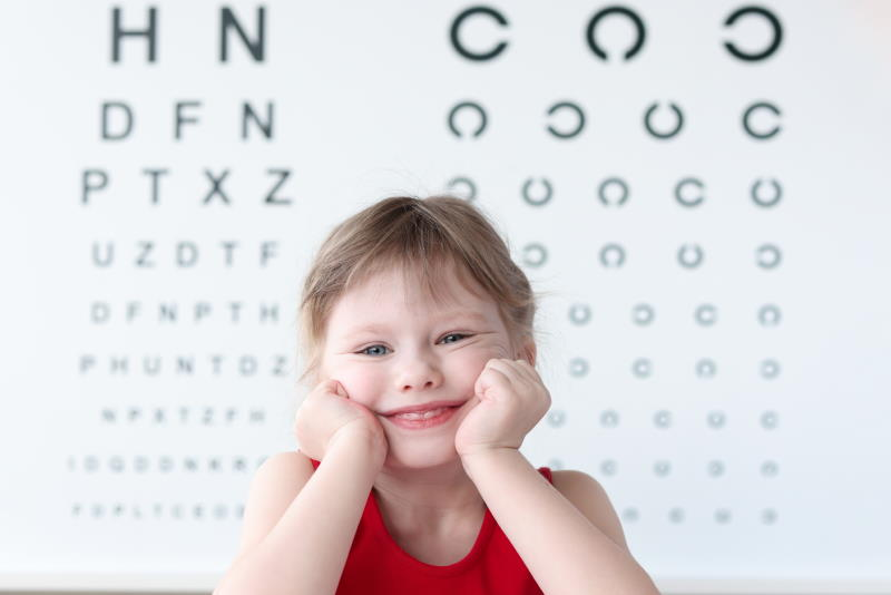 smiling-little-child-against-vision-test-table-in-medical-clinic-portrait